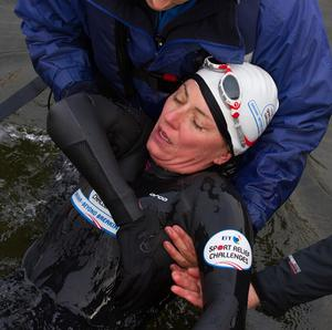 Davina McCall is helped from the water as she completes her swim across Lake Windermere
