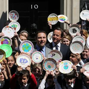 David Walliams poses with Prime Minister David Cameron and some school children on the steps of 10 Downing Street
