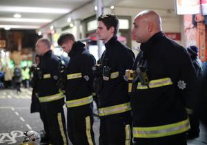 Firefighters pay their respects as people take part in a silent walk to mark the six month anniversary of the Grenfell Tower fire (Yui Mok/PA)