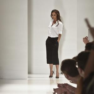 Victoria Beckham takes her applause after her latest runway collection is shown in New York