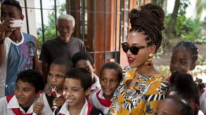 Beyonce poses for photos with school children as she tours Old Havana, Cuba (AP)