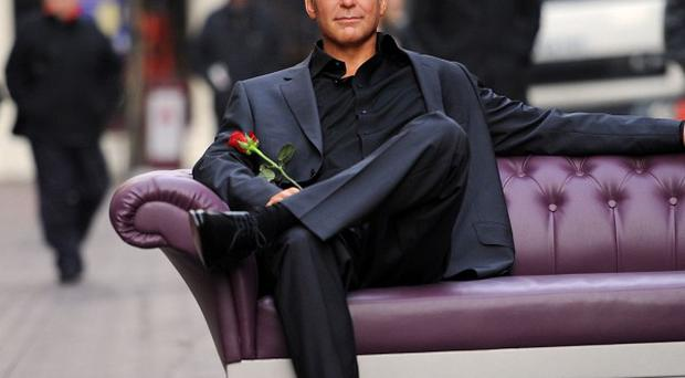 A Madame Tussauds' wax work figure of actor George Clooney in London's Carnaby Street today where members of the public were invited to sit next to the Hollywood star to help celebrate St Valentine's Day. PRESS ASSOCIATION Wednesday February 13 2013. Photo credit should read: Stefan Rousseau/PA Wire