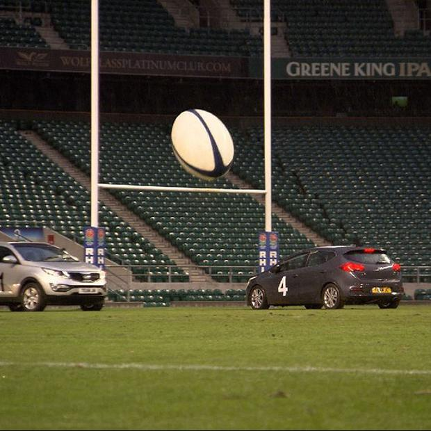 The Top Gear team take part in a game of rugby on wheels on the pitch at Twickenham