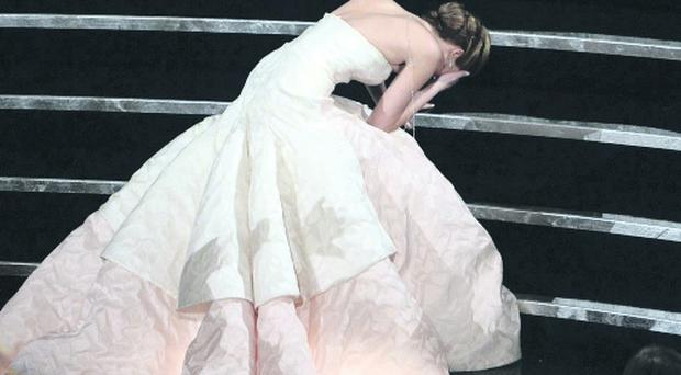 Jennifer Lawrence trips on the stage on her way to collect her Oscar