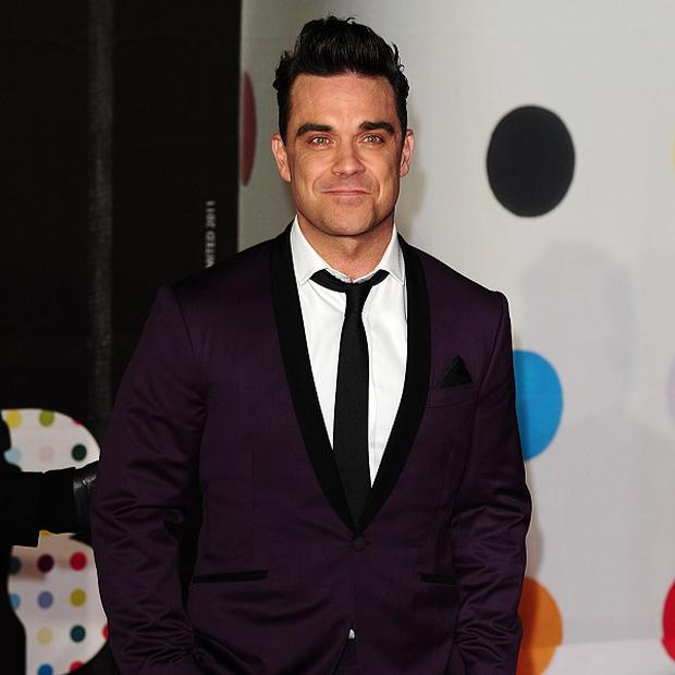 "File photo dated 20/2/2013 of Robbie Williams who has shown off the first fruits of his return to working with Guy Chambers with an expletive-fuelled track in which he branded the Brit Awards ""boring"". PRESS ASSOCIATION Photo. Issue date: Tuesday February 26, 2013. The singer has teamed up with Chambers, his collaborator from the early days of his solo career, to work on a batch of new material. See PA story SHOWBIZ Williams. Photo credit should read: Ian West/PA Wire"
