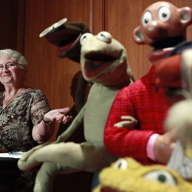 Jane Henson, left, with some of Jim Henson's early puppets, including the original Kermit