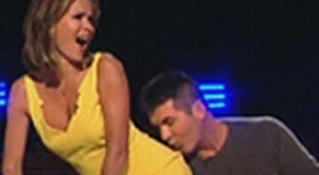 Simon Cowell kisses Amanda Holden's rear during the BGT auditions