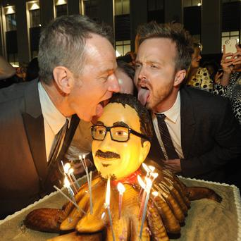 Bryan Cranston and Aaron Paul pose with a cake of Vince Gilligan's face
