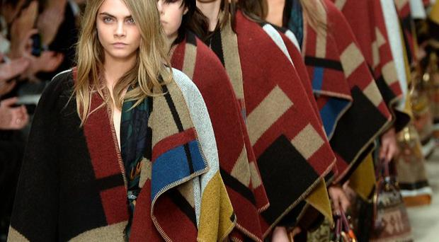 Cara Delevingne leads out models onto the catwalk during the Burberry show