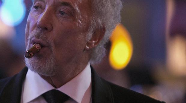 Sir Tom Jones smokes a cigar during a gala dinner marking the end of the 16th annual Cigar Festival in Havana (AP)