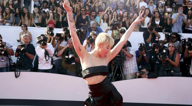 The young homeless man who accompanied Miley Cyrus to the MTV Video Music Awards is wanted by police (AP)