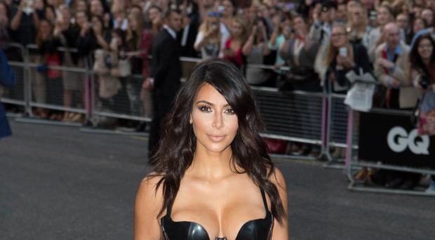 Kim Kardashian was apparently jostled by someone waiting in a large crowd at a Paris Fashion Week event