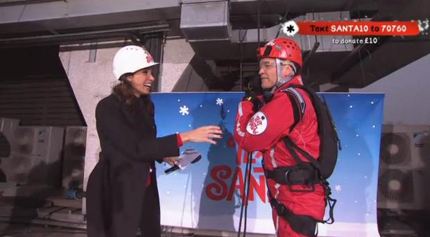 Phillip Schofield is greeted by Christine Bleakley after he abseiled down the exterior of ITV's headquarters as part of his efforts to broadcast continually for 24 hours.