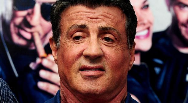 Sylvester Stallone posed for a picture with three tourists who had run up the