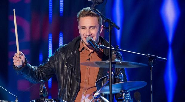 Ross Harris plays the drums while singing