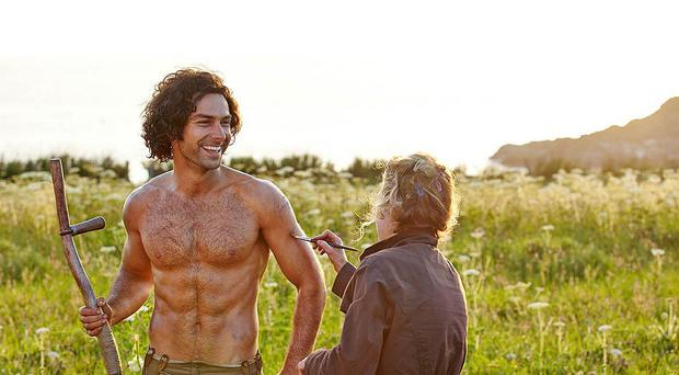 Poldark star Aidan Turner gets the brush-off from a crew member in this behind-the-scenes shot from the BBC costume drama