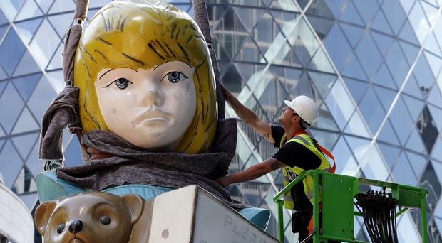 Workers install the sculpture by Damien Hirst opposite the Gherkin in London's Square Mile