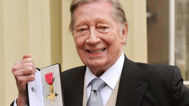 Jeremy Lloyd proudly holds his Officer of the British Empire (OBE) medal.
