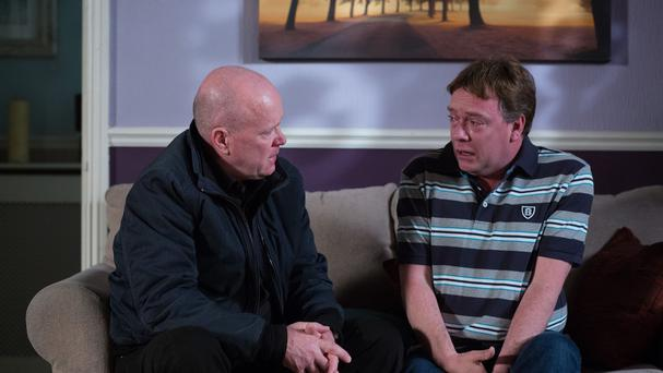 Phil Mitchell, played by Steve McFadden (left), as he comforts Ian Beale, played by Adam Woodyatt, after the murder of his daughter Lucy.