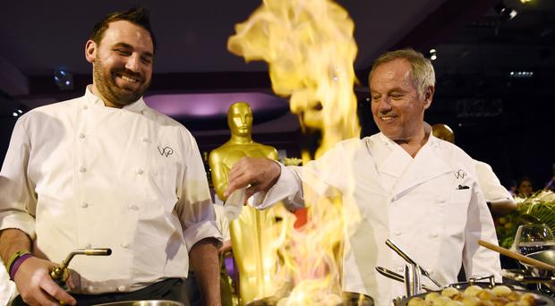 Wolfgang Puck, right, and pastry chef Tyler Atwell pour raspberry liqueur on doughnuts during the Governors Ball press preview (AP)