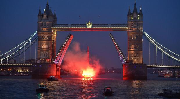 The Sport Relief Hell On High Seas celebrity crew hold flares as their boat passes under Tower Bridge