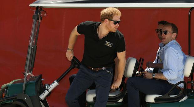 Prince Harry steps from a golf buggy during the Land Rover Discovery Jaguar challenge at Invictus Games 2016