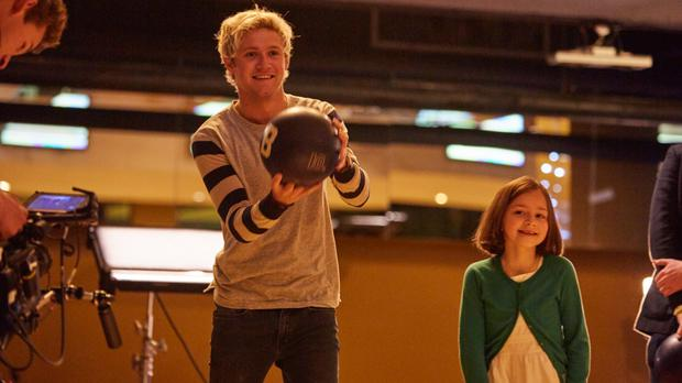 One Direction star Niall Horan at a bowling alley with eight-year-old Luna Caden (PA/Cancer Research UK)