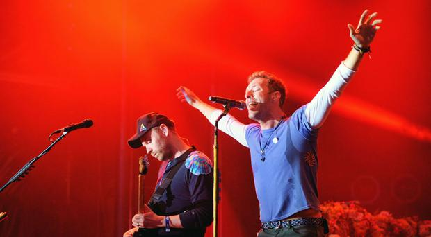 Chris Martin (right) of Coldplay performing during a concert hosted by Prince Harry's charity Sentebalein Kensington Palace Gardens, London.