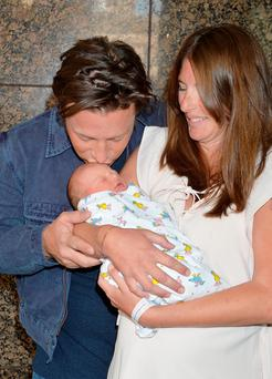 Baby gets a tender kiss from dad Jamie Oliver as his wife Jools looks on