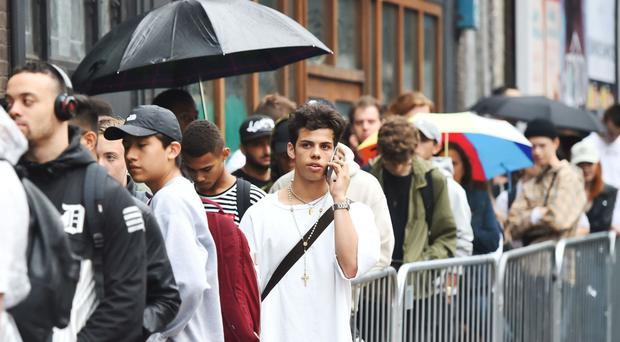 Fans queue in the rain