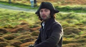 Aidan Turner rides over heathland on Gwennap Head on the Cornish coast during filming for series three of the BBC One drama Poldark