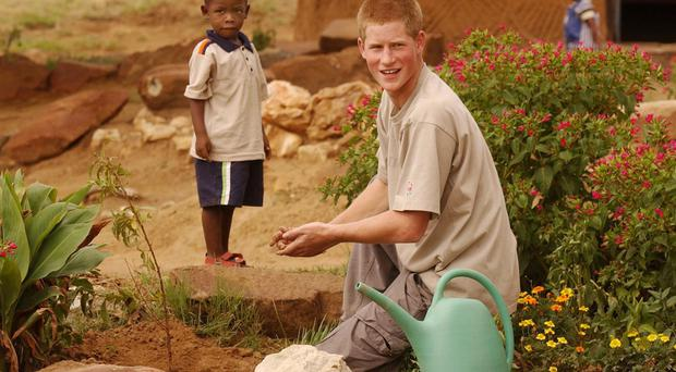 Prince Harry with young orphan Mutsu Potsane, 4, after they planted a peach tree together at the Mants'ase Children's Home for orphans near Mohale's Hoek, in Lesotho