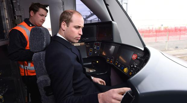 The Duke of Cambridge sounds the warning horn on a Crossrail train during a visit to Bombardier Transportation in Derby