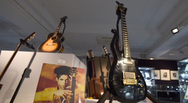 A guitar owned by Prince (front right) and a guitar owned by Jimi Hendrix (back left) on display ahead of the the Entertainment Memorabilia Sale at Bonhams