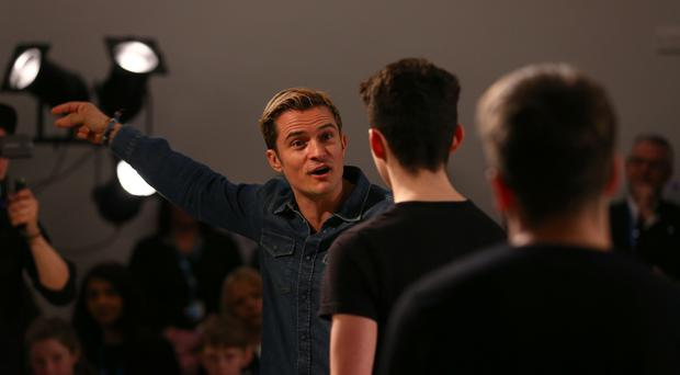 Actor Orlando Bloom gives advice to pupil Max Evans whilst attending the Laurus Trust launch held at Cheadle Hulme High School