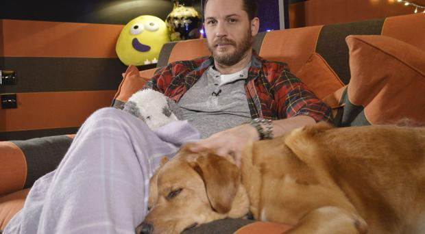 Tom Hardy cuddles up to his dog for his new role - as a bedtime storyteller on CBeebies (BBC/PA)