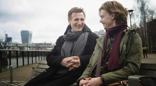 Liam Neeson (left) as Daniel and Thomas Brodie -Sangster as Sam, during filming for Red Nose Day Actually on the South Bank in London.