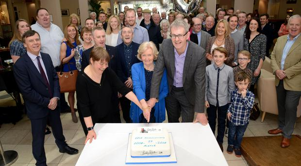 Professor Ruth Plummer, Lady Elsie and Mark Robson cutting a cake surrounded by Sir Bobby Robson Foundation supporters, (Sir Bobby Robson Foundation/PA)