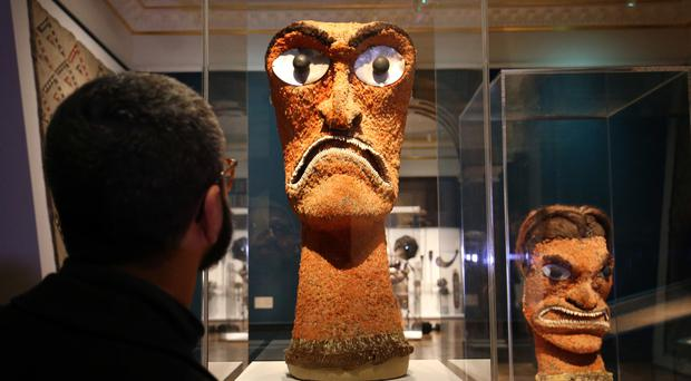 A visitor looks at two examples of Akua Hulu Manu, feathered god images, during a press view for Oceania at the Royal Academy (Jonathan Brady/PA)