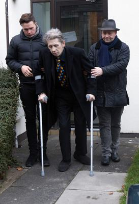 A frail Shane MacGowan leaves his home on crutches for the funeral