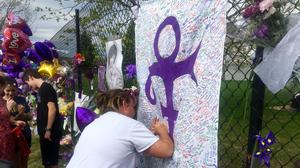 A woman writes on memorial sheet adorned with the symbol Prince once used to identify himself outside Paisley Park (AP)