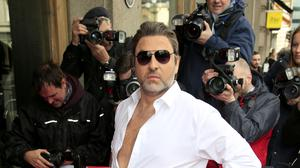 Walliams arrived on the red carpet at the event held in central London sporting Cowell's trademark sunglasses, black trousers pulled up high and a white shirt with a bit of chest exposed