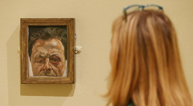 A gallery employee looks at Self Portrait With A Black Eye by Lucian Freud during a preview of Lucian Freud: The Self-portraits exhibition at the Jillian and Arthur M. Sackler Wing of Galleries, Royal Academy of Arts, London (Jonathan Brady/PA)