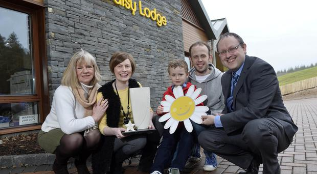 Blooming: Chief Executive of the Cancer Fund for Children Centre Gillian Creevy, the Rea family (Christine, Joel and Jonathan) and Belfast Telegraph Sports Editor Steven Beacom with Rory McIlroy's award