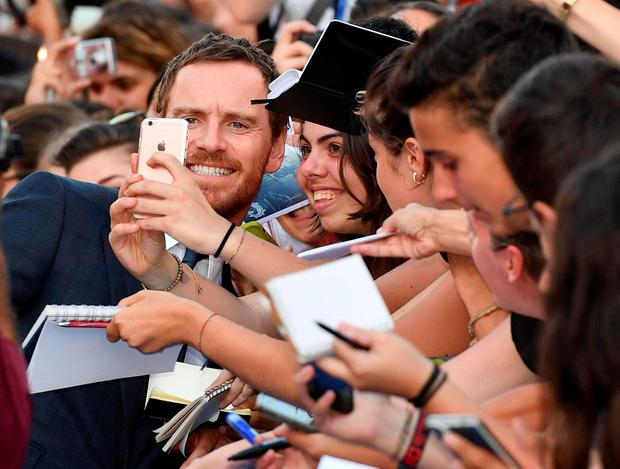 German-Irish actor Michael Fassbender signs autographs as he arrives for the premiere of 'The light between oceans' during the 73rd Venice Film Festival in Venice, Italy, Thursday, Sept. 1, 2016. (Ettore Ferrari/ANSA via AP)