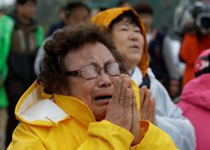 One of relatives of passengers aboard a sunken ferry cries during a Buddhist ceremony to pray for speedy rescue and their safety at a port in Jindo, south of Seoul, South Korea, Friday, April 18, 2014. The ferry flipped onto its side and filled with water off the southern coast of South Korea on Wednesday, with about 270 people still missing. (AP Photo/Lee Jin-man)