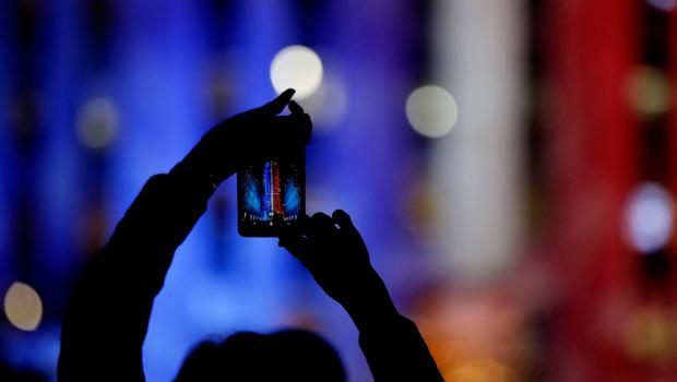 A person photographs the 30 Rockefeller building illuminated in patriotic lights during an Election Night gathering at Rockefeller Center, Tuesday, Nov. 8, 2016, in New York. (AP Photo/Julio Cortez)