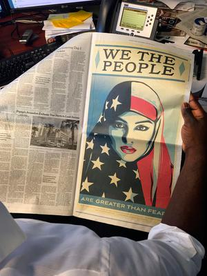 A poster-size image of a woman in a headscarf in the colors of the American flag is viewed as it appeared in a full-page ad in several US newspapers on January 20, 2017, part of a protest launched on the day of Donald Trump's presidential inauguration. AFP/Getty Images