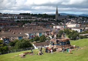 People build a bonfire in the bogside area of Londonderry, which is traditionally torched on August 15 to mark a Catholic feast day celebrating the assumption of the Virgin Mary into heaven, but in modern times the fire has become a source of contention and associated with anti-social behaviour. PRESS ASSOCIATION Photo. Picture date: Tuesday August 15, 2017. Disorder flared in Londonderry on Monday night as bonfire-builders attacked police and members of the public. Police said those gathered at the controversial fire site in Derry's Bogside threw rocks and stones at local people before targeting police with petrol bombs and other missiles. See PA story ULSTER Bonfire. Photo credit should read: Niall Carson/PA Wire