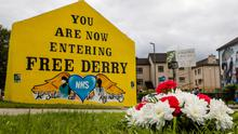 Flowers and a message to the late John Hume rest below Free Derry Corner in the Bogside area of the city. Pic: Liam McBurney/PA Wire
